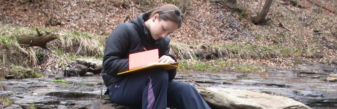 Woman taking notes by stream