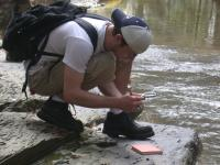 Student studying by river bed